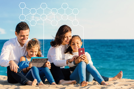 Close up outdoor portrait of young parents sitting with kids on beach. Family looking and laughing together at digital tablet and smartphone. Conceptual digital structure floating in sky above. Zdjęcie Seryjne