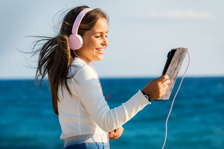 Close up outdoor portrait of cute young girl wearing headphones.Smiling tween holding digital tablet against blue sea and sky.