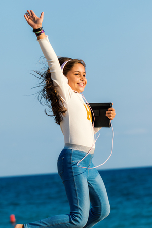 Close up action portrait of smiling tween girl jumping with headphones and tablet on beach. Girl raising arm against sea and sky background.