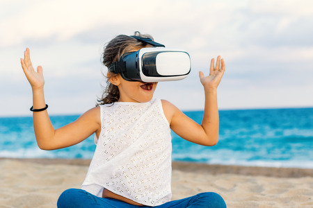 Close up portrait of little girl having fun with virtual reality glasses.Kid with open mouth raising arms.