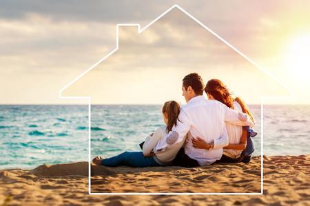 Concettuale nel tardo pomeriggio ritratto all'aperto di giovani genitori seduti sulla spiaggia con i bambini.Quattro restituendo contro il mare e lo sfondo del cloud. Icona della casa che disegna intorno alla famiglia.