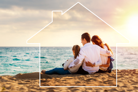 Conceptual late afternoon outdoor portrait of young parents sitting on beach with kids.Foursome giving back against sea and cloud background. House icon drawing around family. Banque d'images