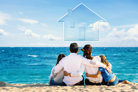 Conceptual happy family portrait of young couple sitting with kids on beach. Rear view of foursome against blue sea and floating house icon above in clouds.
