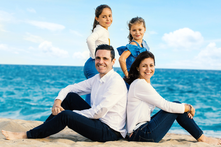 Full length outdoor portrait of attractive young couple with children. Happy family  sitting together on beach looking at camera. Zdjęcie Seryjne