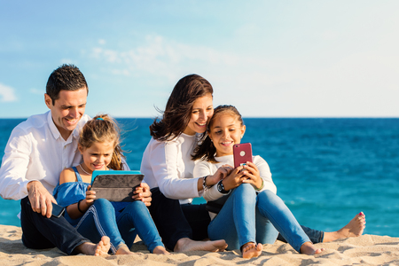 Close up outdoor portrait of young parents sitting with kids on beach. Family looking and laughing together at digital tablet and smartphone. Zdjęcie Seryjne