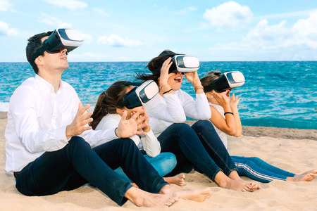 Close up portrait of young family having virtual reality fun with VR glasses. Foursome sitting together on beach.