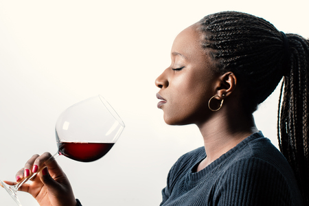Close up side view portrait of African female wine enthusiast smelling red wine aroma. Woman with braided hair and eyes closed isolated against white background.