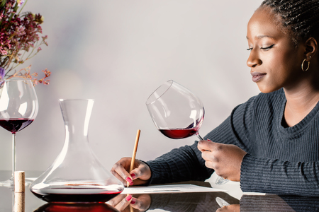 Close up portrait of attractive african woman with braids evaluating red wine at table. Girl taking notes next to decanter.