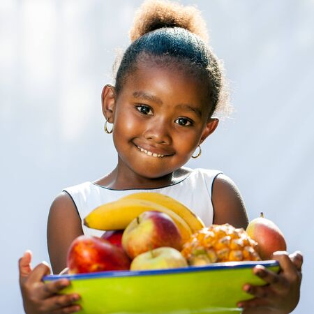 Close up portrait of cute African girl holding fruit bowl.Isolated against light background. Banque d'images