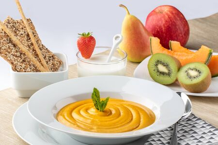 Close up of appetising health diet menu with pumpkin soup, kefir, sesame seed crackers and fresh fruit. 版權商用圖片 - 131431114