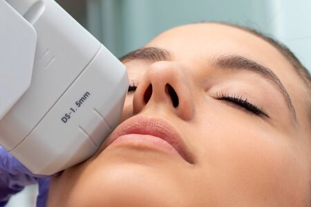 Extreme close up of HIFU treatment on female face. Therapist doing cosmetic plasma lift with high intensity focal ultrasound device. Banque d'images