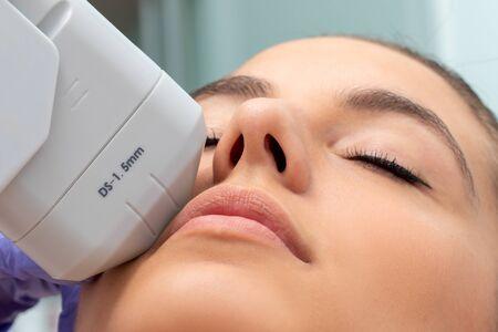 Extrême gros plan du traitement HIFU sur le visage féminin. Thérapeute faisant un lifting plasma cosmétique avec un appareil à ultrasons focal de haute intensité.