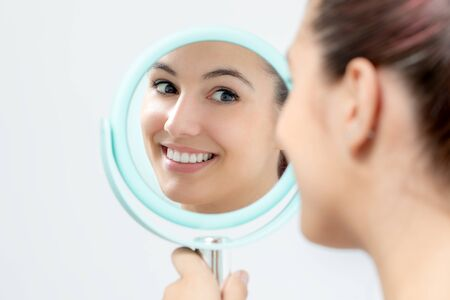 Close up portrait of young woman looking in mirror at herself. Girl with healthy white teeth holding hand mirror.