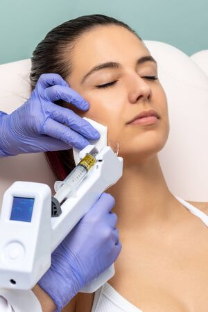 Woman having cosmetic facial plasma lift with micro needle gun.