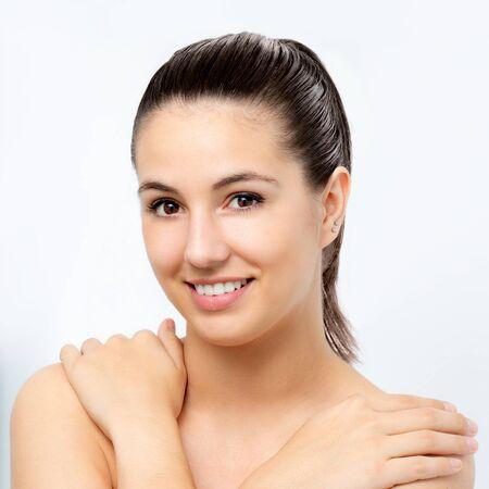 Chiuda sul ritratto di bellezza di giovane donna attraente con le mani sulle spalle. Ragazza con pelle sana isolata su fondo bianco.