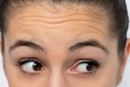 Close up detail of woman looking aside frowning forehead. Prominent wrinkles shown on skin. Stock Photo