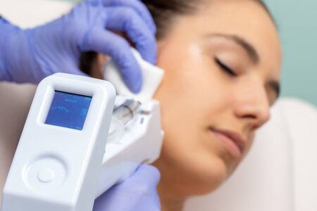Micro needling technology used on young woman. Device with digital screen indicating depth applied on skin. Stock fotó - 131430898