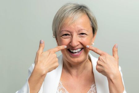 Close up studio portrait of laughing middle aged woman pointing at wrinkles along cheek.
