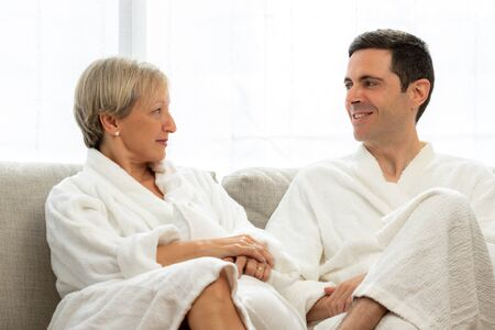 Close up portrait of middle aged couple in white bathrobes at home. Couple looking at each other on couch.
