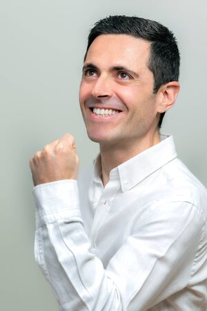 Close up studio portrait of attractive middle aged man in white shirt pulling a fist. Man with positive attitude looking above. Isolated on light background. Zdjęcie Seryjne