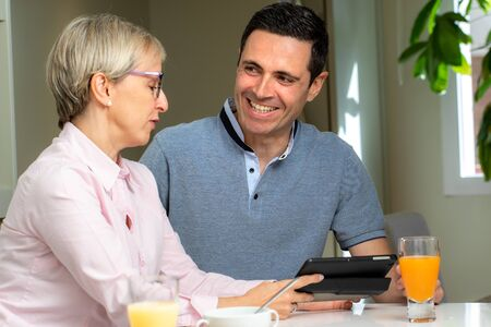 Close up portrait of middle aged  couple together at home. Couple having conversation at breakfast table with digital tablet.