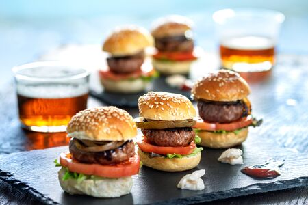 Close up of multiple appetizing mini beef hamburgers with small beers on bar table. Zdjęcie Seryjne