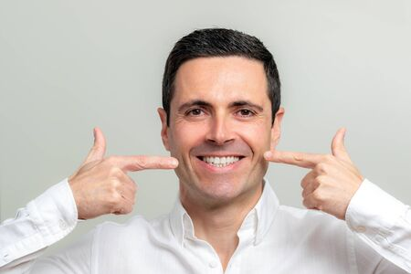Close up studio portrait of attractive smiling middle aged man pointing with fingers at wrinkles along cheek.
