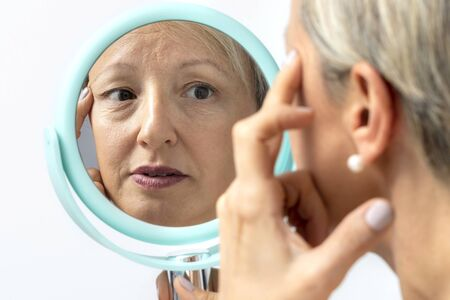 Close up portrait of middle aged woman looking at sagging skin in hand mirror. Reflection of woman showing under eye wrinkles. Zdjęcie Seryjne