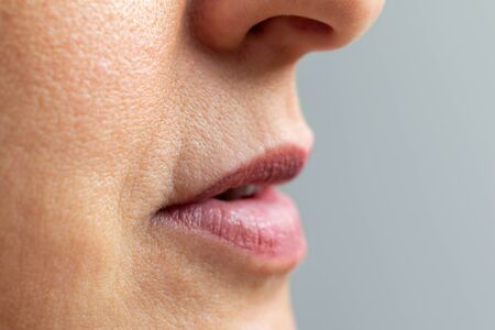 Close up macro detail of wrinkles around mouth and lips of middle aged woman.