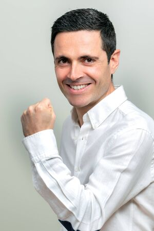 Close up studio portrait of attractive middle aged man in white shirt pulling a fist. Man with positive attitude looking at camera. Isolated on light background. Zdjęcie Seryjne