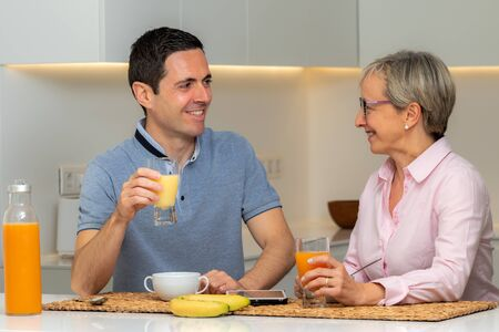 Close up portrait of middle aged couple having breakfast together at home. Couple in casual wear drinking fruit juice at table.