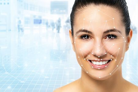 Close up portrait of attractive caucasian woman with facial recognition technology. Grid with reference areas marked on face. Young girl against out of focus airport background. Zdjęcie Seryjne