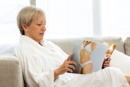 Side view portrait of middle aged woman in white bathrobe reading on couch. Woman looking at healthcare treatment magazine.