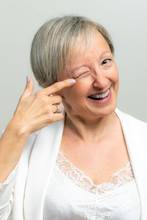 Close up studio portrait of smiling middle age woman pointing with finger at wrinkles next to eye. Woman indicating at face with one eye closed.