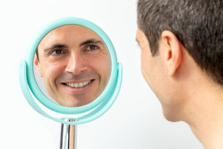 Close up portrait of middle aged man with reflection in hand mirror. Isolated on light background.
