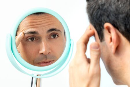 Close up portrait of middle aged man reviewing wrinkles and sagging skin in hand mirror. Isolated on light background.
