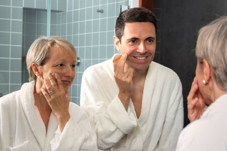 Close up portrait of middle aged couple in bathrobes looking in bathroom mirror. Couple reviewing sagging skin and signs of ageing.