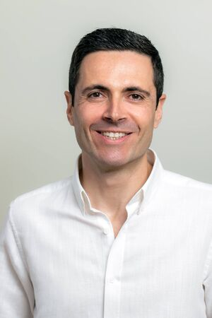Close up studio portrait of attractive middle aged man in white shirt looking at camera. Man with charming smile isolated on light background.