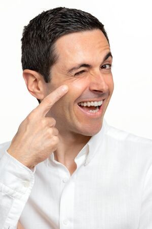 Close up studio portrait of middle age man pointing with finger at crow's feet next to eye. Fun portrait with happy facial expression. Isolated on white background.