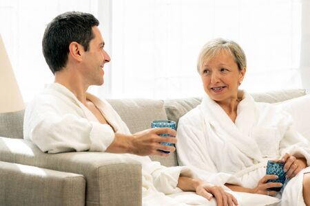 Close up portrait of middle aged couple having a conversation at home. Couple in white bathrobes sitting on couch holding glasses.