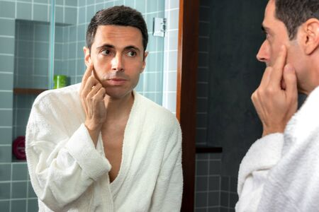 Close up portrait of middle aged man in bathrobe reviewing wrinkles and sagging skin in bathroom mirror.