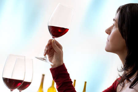 Close up portrait of female enologist evaluating red wine. Side view of woman holding red wine glass against seamless background. Stok Fotoğraf - 150728344