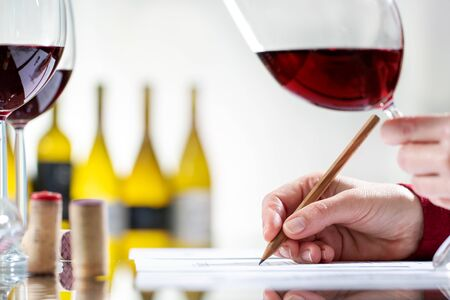 Close up detail of enologist writing notes on wine evaluation at table. Out of focus bottles in background.