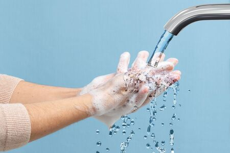 Close up detail of female hands disinfecting with soap under chrome tap with running water. Zdjęcie Seryjne