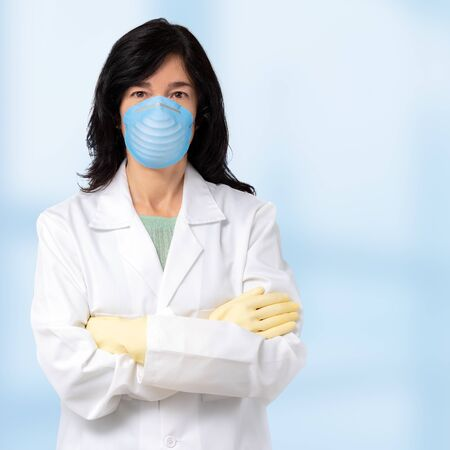 Close up portrait of female doctor wearing surgical mask and gloves