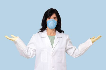 Close up portrait of female doctor with face mask raising hands next to body with blank body language.
