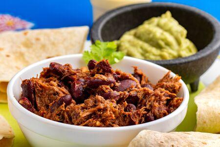 Close up traditional Mexican chili with meat dish. Grilled meat with garlic, onions, tomatoe and red beans. Banque d'images