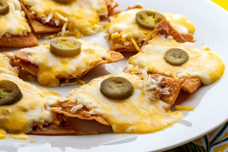 Macro close up of appetizing mexican with melted cheese and and hot tasty jalapeño chillies. Stok Fotoğraf