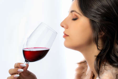 Close up portrait of wine lover smelling red wine aroma against light seamless background. Stok Fotoğraf - 153067507