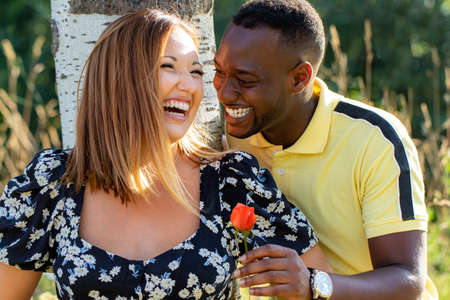 Close up portrait of charming african young man giving caucasian girlfriend a flower outdoor park. Romantic diverse couple laughing together. Stok Fotoğraf - 153324553